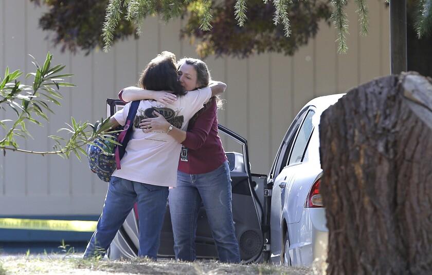 Two women embrace outside Rancho Tehama Elementary School.
