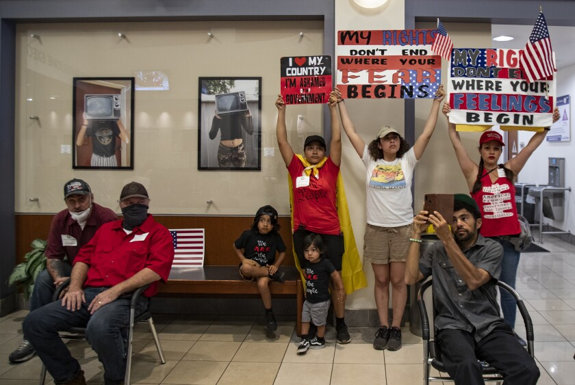 Protesters who want public health orders rescinded watch and listen to video monitors during the Riverside County Board of Supervisors meeting on May 5 in Riverside, Calif.