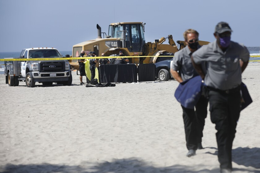 A tractor, truck and caution tape on a beach. Two people carry a gurney