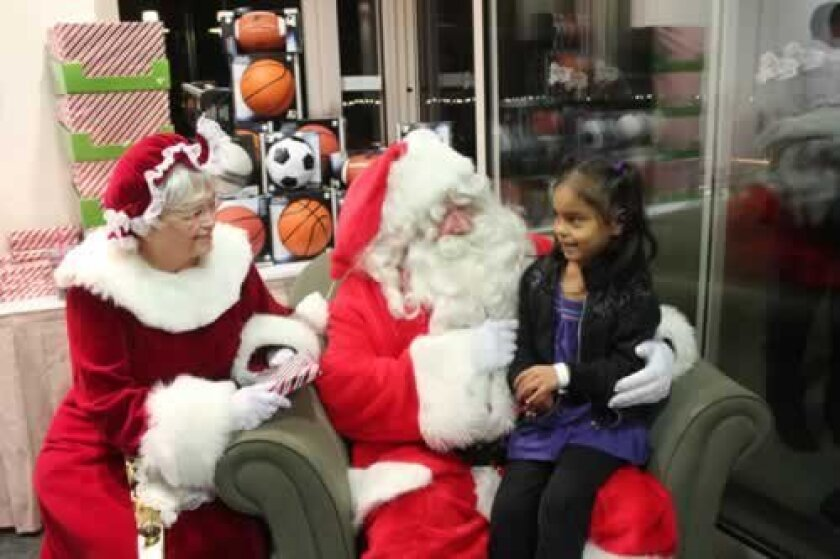 Alexis, 5, sits with Santa and Mrs. Claus. Ashley Mackin