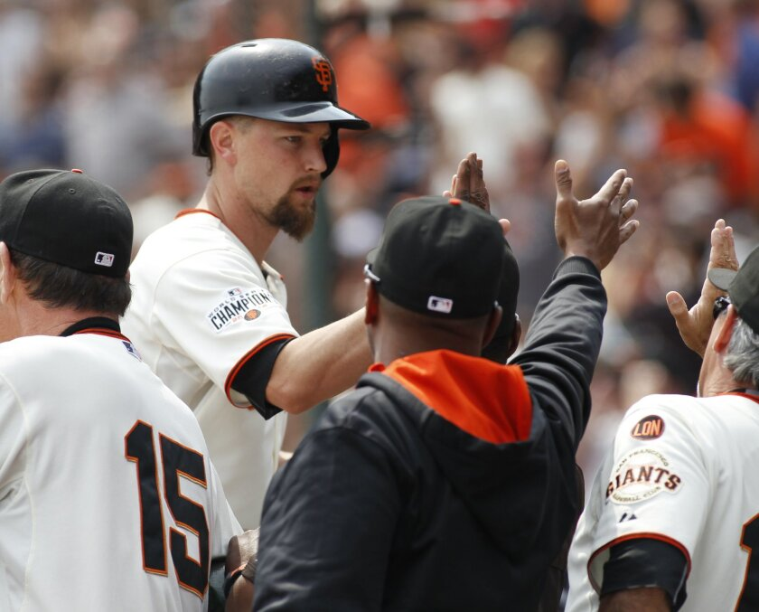 San Francisco Giants Mike Leake is greeted at the dugout after hitting a three run homer against the San Diego Padres during the second inning of a baseball game, Sunday, Sept. 13, 2015, in San Francisco. (AP Photo/George Nikitin)