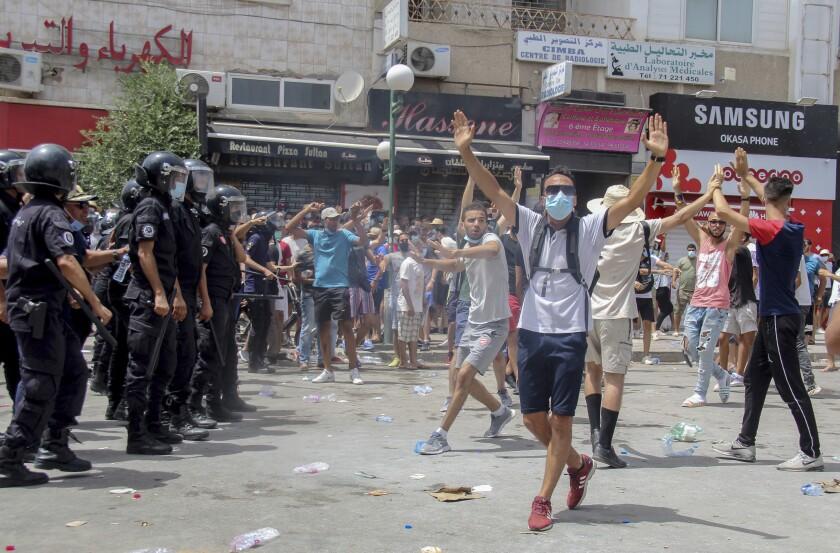 Manifestantes ante varios policías tunecinos durante una protesta en Túnez, capital de Túnez, el domingo 25 de julio de 2021. (AP Foto/Hassene Dridi)
