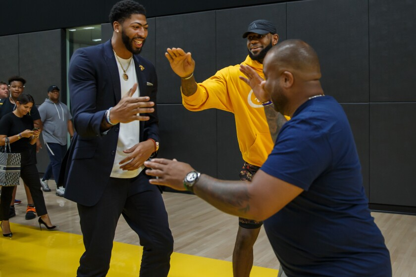 Anthony Davis greets  fellow teammate LeBron James and LeBron's friend, Randy Mims, after Davis' press conference at the UCLA Health Training Center in El Segundo.