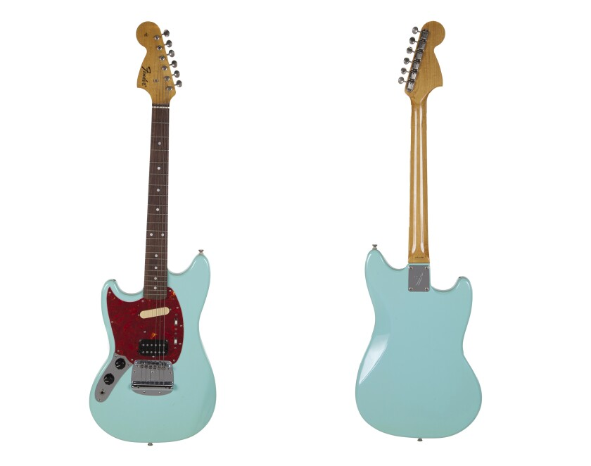 This combination photo of images released by Julien's Auctions shows the front and back of a turquoise-bodied left-handed Fender guitar built in 1993 and used by Nirvana frontman Kurt Cobain during the band's In Utero tour. The item is one of many rock and roll items up for auction on Oct. 25 and 26. (Julien's Auctions via AP)