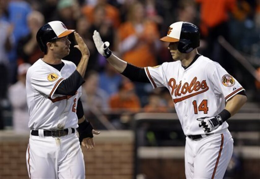 Baltimore Orioles' J.J. Hardy, left, high-fives teammate Nolan Reimold after being batted in on a home run by Reimold in the second inning of a baseball game against the Tampa Bay Rays on Thursday, April 18, 2013, in Baltimore. (AP Photo/Patrick Semansky)