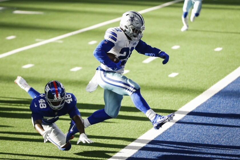 Cowboys Ezekiel Elliott leaps out of the way to a touchdown during the game against New York Giants Sunday, Oct. 11, 2020, in Arlington, Texas. (Yffy Yossifor/Star-Telegram via AP)