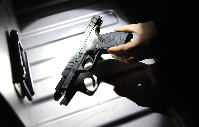 A California Department of Justice law enforcement officer holds a firearm belonging toa Whittier man who was not legally allowed to possess a handgun.