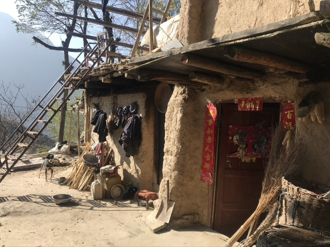 Signs of life including hanging laundry and doorway decorations in ane abandoned village in Lianghekou.