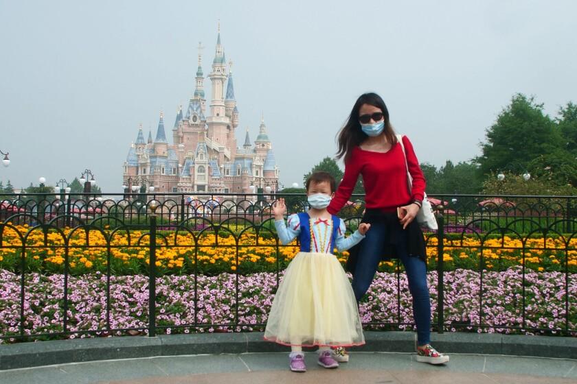 Visitors wearing face masks visit the recently reopened Shanghai Disneyland.