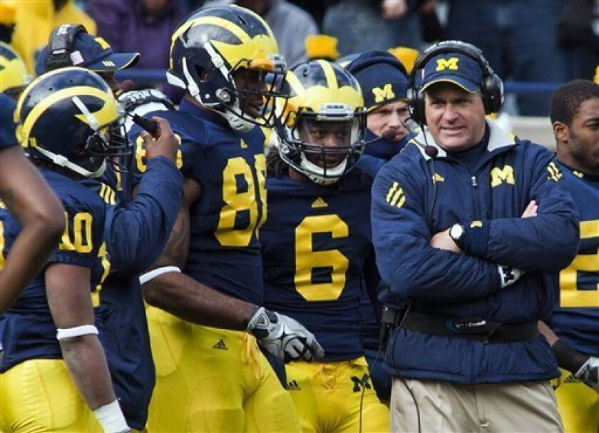 FILE - In this Nov. 6, 2010, file photo, Michigan head coach Rich Rodriguez, right, gathers with players on the sideline during a timeout in the second quarter of an NCAA college football game against Illinois in Ann Arbor, Mich. Two people familiar with the situation say Rodriguez is still meeting with his boss. The meeting between Rodriguez and athletic director Dave Brandon stretched late into Tuesday afternoon, Jan. 4, 2011, amid two reports that Rodriguez will be fired. (AP Photo/Tony Ding, File)