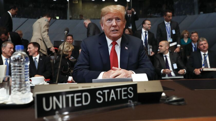 U.S. President Donald Trump takes his seat as he attends the multilateral meeting of the North Atlantic Council in Brussels, Belgium.