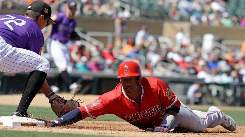Angels' Yunel Escobar dives back to first as Rockies first baseman Jordan Patterson takes the throw during a spring training game on Mar. 16 in Scottsdale, Ariz.