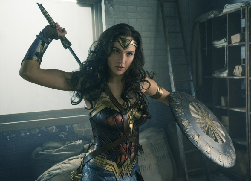 """Gal Gadot reaches for a weapon in a scene from the film """"Wonder Woman."""""""