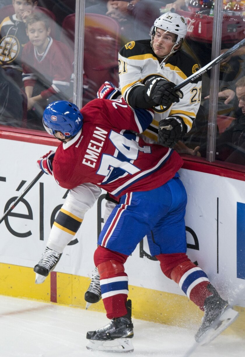 Boston Bruins' Loui Eriksson, right, is checked into the boards by Montreal Canadiens' defender Alexei Emelin during first period NHL hockey action, in Montreal, on Saturday, Nov. 7, 2015. (Paul Chiasson/The Canadian Press via AP)