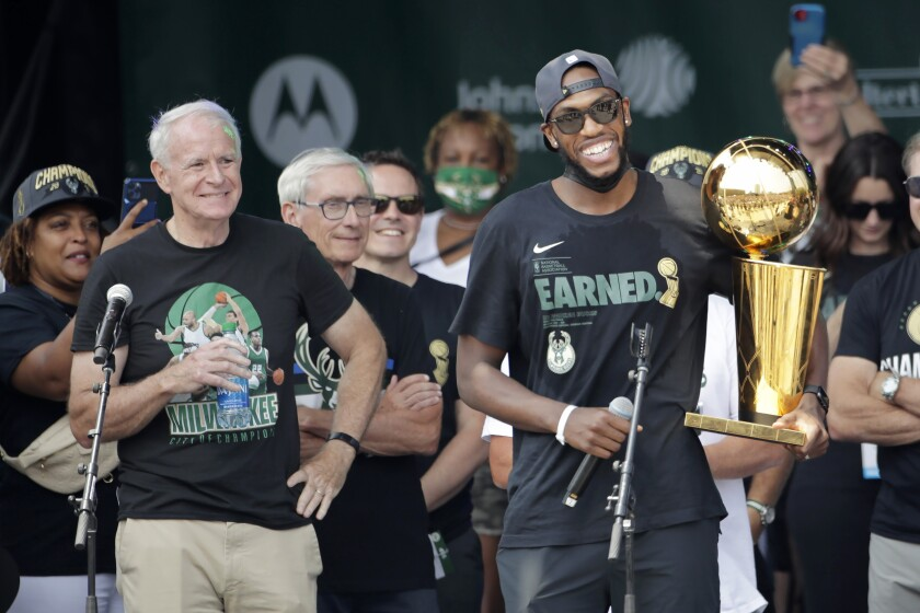 Milwaukee Bucks' Khris Middleton smiles with the NBA Championship trophy during a parade celebrating the Milwaukee Bucks' NBA Championship basketball team Thursday, July 22, 2021, in Milwaukee. (AP Photo/Aaron Gash)