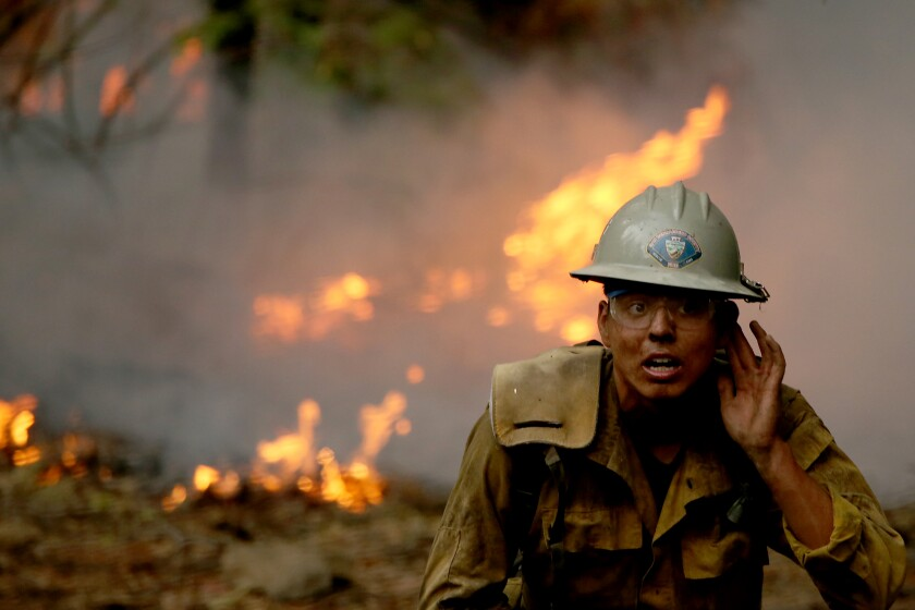 JANESVILLE, CALIF. - AUG. 189 2021. A firefighter battles the Dixie Fire in the mountainous and forested terrain near Janesville on Thursday, Aug. 19, 2021. (Luis Sinco / Los Angeles Times)