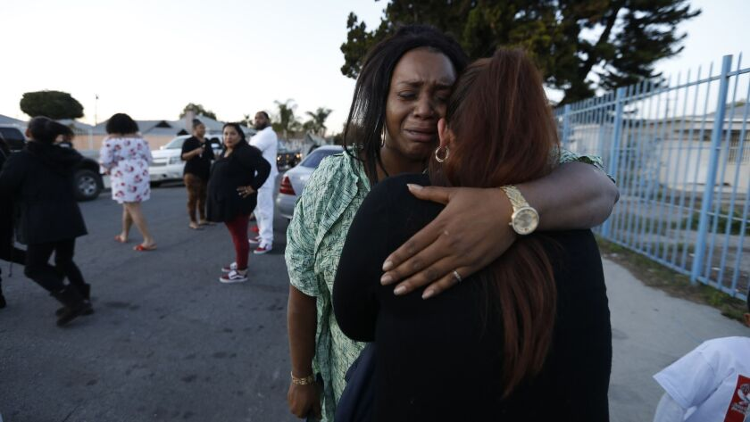 Amira Webster, left, hugs a woman after Webster's brother was killed and two others were wounded Friday in a shooting outside a church in Compton.