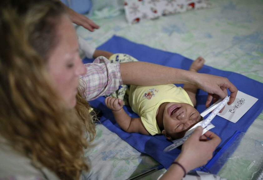 Pediatrician Alexia Harrist from the United States' Centers for Disease Control and Prevention (CDC) examines 3-month-old Shayde Henrique, who was born with microcephaly, in Joao Pessoa, Brazil, Tuesday, Feb. 23, 2016. U.S. and Brazilian health workers knocked on doors in the poorest neighborhoods of one of Brazil's poorest states Tuesday in a bid to enroll mothers in a study aimed at determining whether the Zika virus is really causing a surge in birth defects. The teams started in Joao Pessoa, the capital of Paraiba state which is one of the epicenters of Brazil's tandem Zika and microcephaly outbreaks. (AP Photo/Andre Penner)