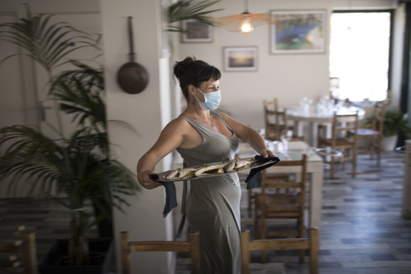 A waitress wearing a face mask to protect against coronavirus carries out a plate of fish to serve at a seafood restaurant in Marseille, southern France, Tuesday, June 2, 2020. The French way of life resumes Tuesday with most virus-related restrictions easing as the country prepares for the summer holiday season amid the pandemic. (AP Photo/Daniel Cole)