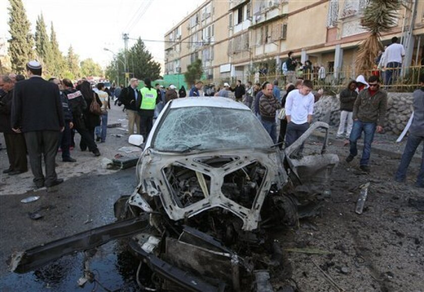 Israelis gather around a car after it was hit by a rocket fired from the Gaza Strip in the southern Israeli town of Beersheeba, Sunday, Jan. 11, 2009. Israeli troops battled Palestinian gunmen in a suburb of Gaza City on Sunday morning as Israel's military inched closer to Gaza's main population ce