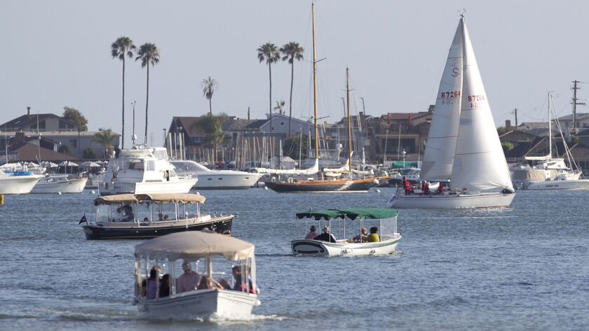 Sailboats and other water craft move through the Newport Harbor turn basin on Wednesday.