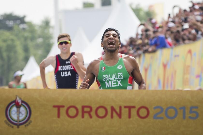 El mexicano Crisanto Grajales (derecha) reacciona al cruzar la meta para ganar la medalla de oro sobre el estadounidense Kevin McDowell en el triatlón masculino de los Juegos Panamericanos en Toronto, el domingo 12 de julio de 2015. (AP Foto/Felipe Dana) ** Usable by HOY and ELSENT Only **