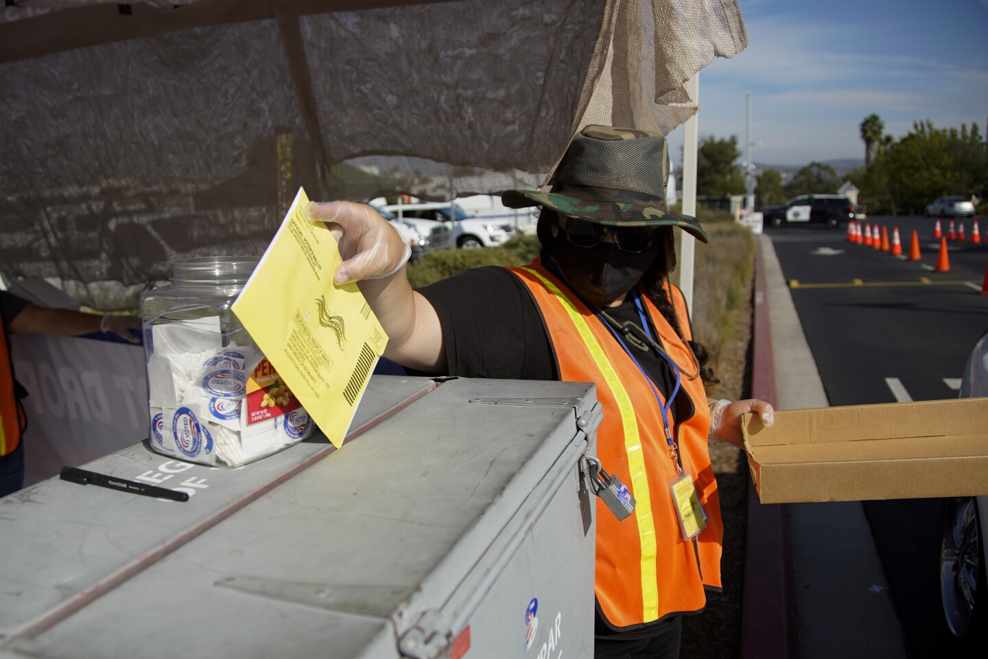 A poll worker drops in a ballot on Election Day.