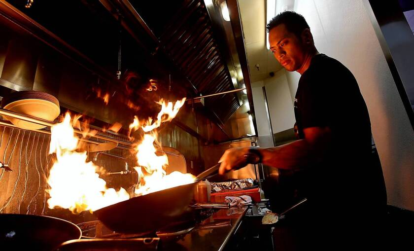 Manager and sous chef Micko Ortiz prepares a wok for cooking.