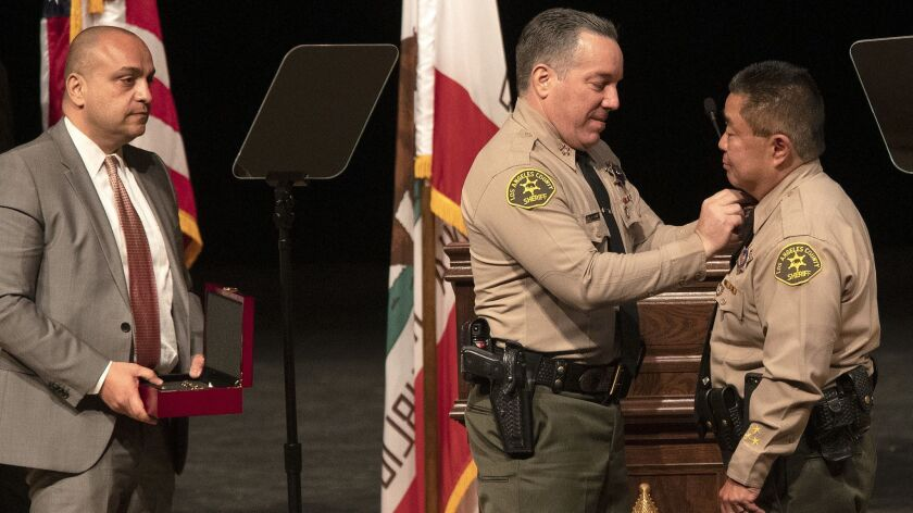 Caren Carl Mandoyan looks on as Alex Villanueva, the new Los Angeles County Sheriff, pins officers during a ceremony in Monterey Park, Calif. on December 3, 2018.