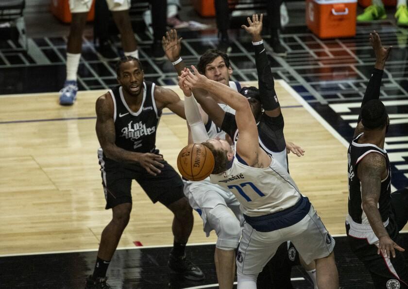 Clippers guard Reggie Jackson and forward Kawhi Leonard, left, force a turnover by Dallas Mavericks guard Luka Doncic.