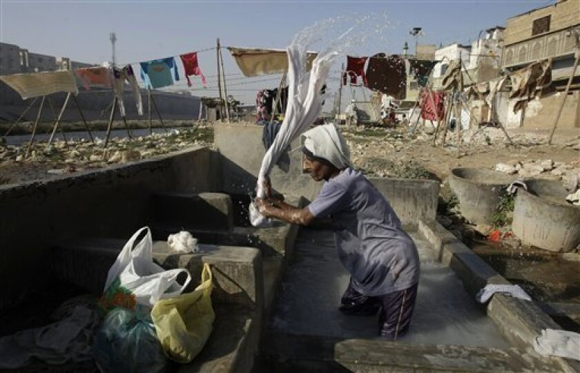 A Pakistani man washes clothes at a local washing pool in Karachi, Pakistan on Thursday, Feb. 2, 2012. (AP Photo/Fareed Khan)