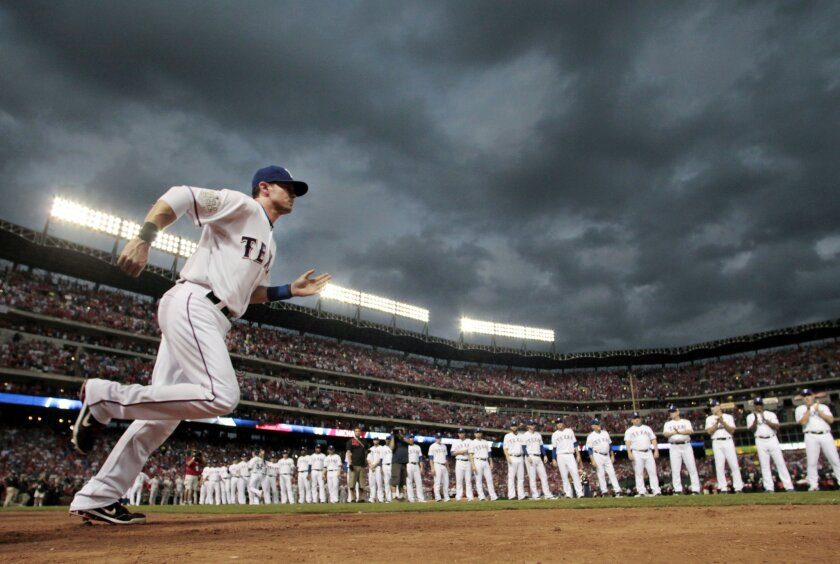 FILE - In this Oct. 22, 2011, file photo, Texas Rangers' Michael Young is introduced before Game 3 of baseball's World Series against the St. Louis Cardinals in Arlington, Texas. Young is retiring after a 13-year major league career, nearly all of it with the Rangers.  The seven-time All-Star retir