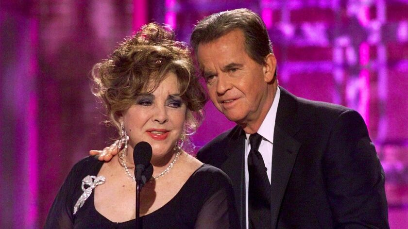 Golden Globes: Dick Clark gives a tipsy Elizabeth Taylor a hand during the presentation of the best picture winner in 2001.