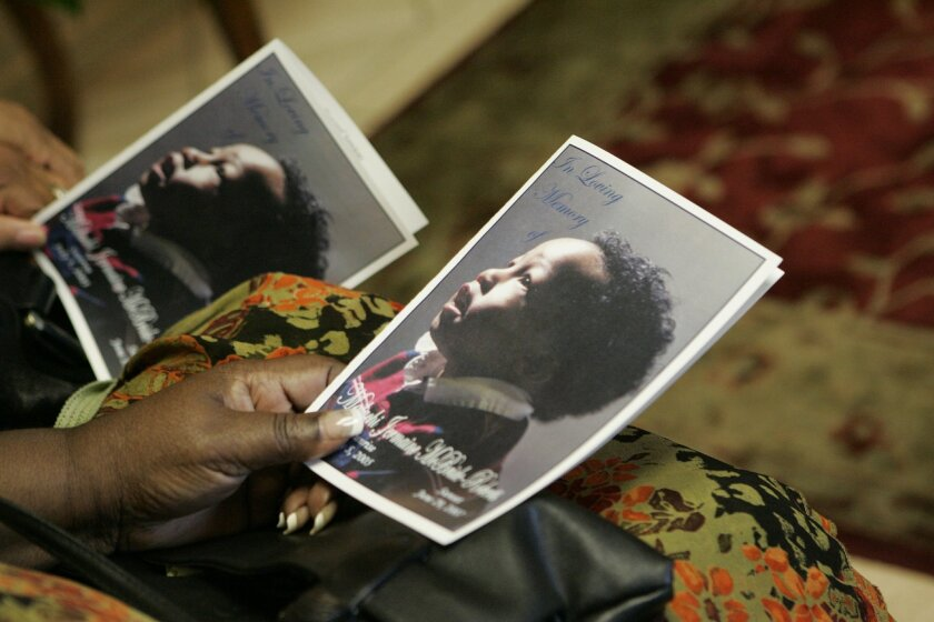 Mourners hold photos of Malachi Roberts-McBride at his funeral in July 2007, just days before he would have turned 2 years old.