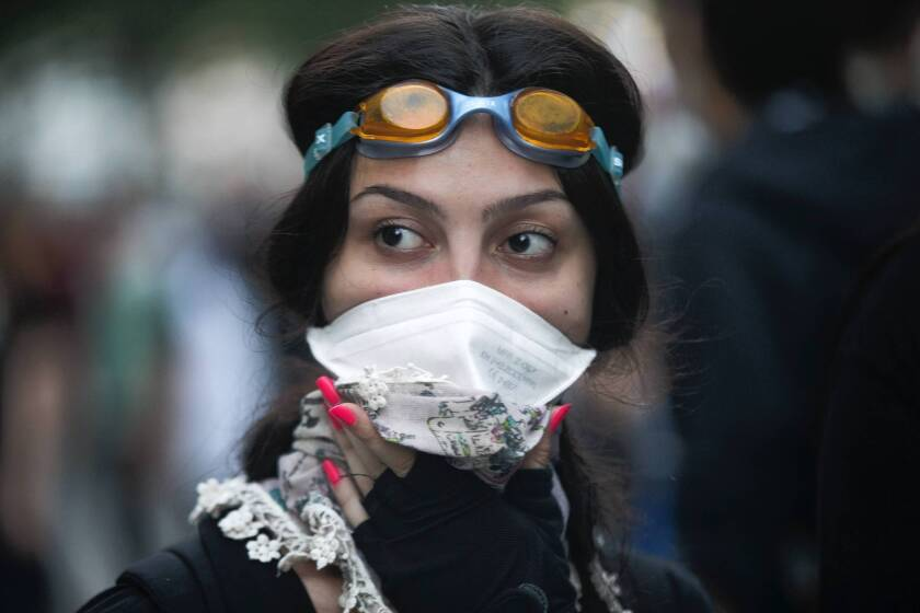 A protester covers her face during clashes with police near the office of Turkish Prime Minister Recep Tayyip Erdogan in Istanbul.
