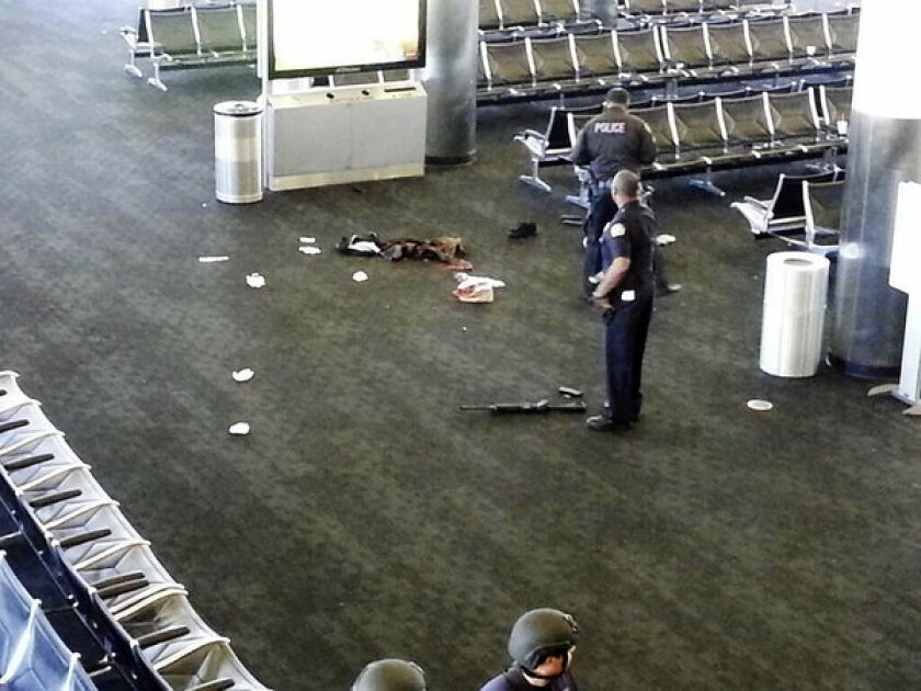At Los Angeles International Airport, police officers stand near a weapon on Nov. 1, 2013, after a gunman opened fire in a terminal, killing Transportation Security Administration officer Gerardo Hernandez and wounding others.