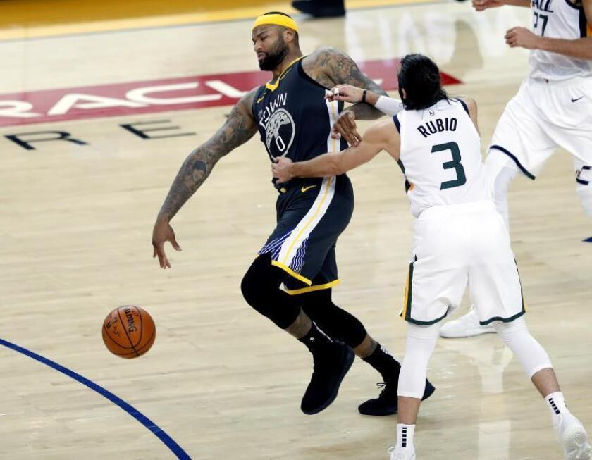 El pívot de los Warriors de Golden Gate DeMarcus Cousins (i) recibe una falta del escolta de los Jazz de Utah el español Ricky Rubio (d) durante el partido de la NBA que enfrentó, este martes 12, a los Jazz de Utah contra los Warriors de Golde State en el Oracle Arena en Oakland, California, Estados Unidos. EFE