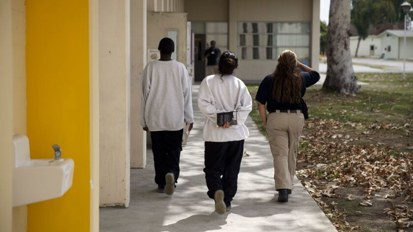 Female minors detained at the juvenile hall are escorted by a probation officer with their books aft