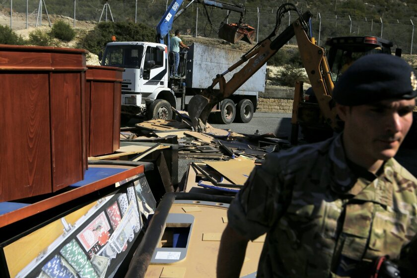 A British soldier passes by the illegal casino identified at a warehouse at Episkopi British military base, near the southern port city of Limassol, Cyprus, Monday, Feb. 22, 2016. Authorities at a British military base in Cyprus used an excavator to smash tens of thousands of euros worth of illegal gambling equipment that were seized in police raids. (AP Photo/Petros Karadjias)