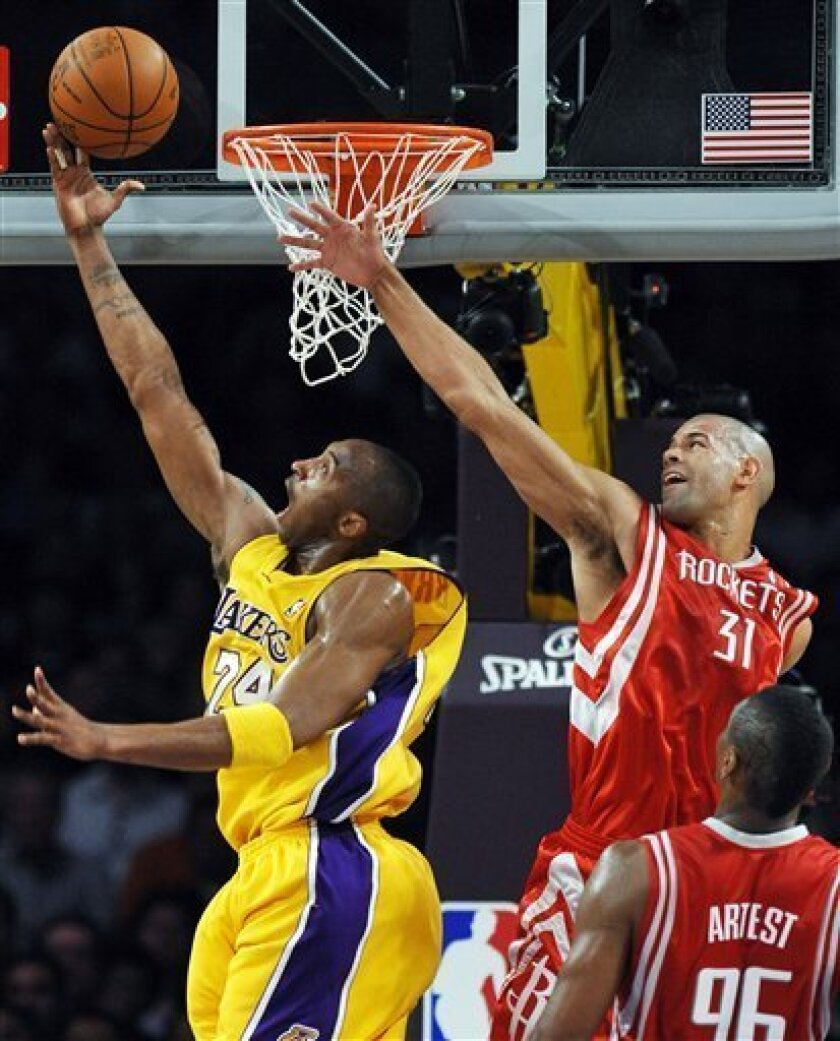 Los Angeles Lakers guard Kobe Bryant, left, goes to the basket past Houston Rockets forward Shane Battier in the first half during Game 5 of a second-round NBA basketball playoff series in Los Angeles, Tuesday, May 12, 2009. (AP Photo/Chris Carlson)