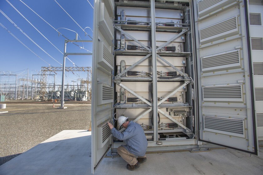 A PG&E worker looks over stacks of battery cells that are part of an experimental project in Vacaville, southwest of Sacramento. The stacks can store enough electricity to power 1,400 homes for a day.