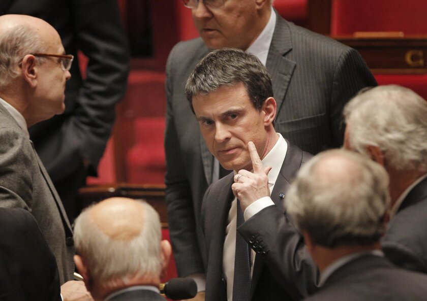 French prime minister Manuel Valls, center, leaves the France's National Assembly, in Paris, Wednesday, Feb. 10, 2016. French lawmakers voted on a divisive bill aimed at changing the constitution to introduce the possibility of revoking the citizenship of people convicted on terrorism charges in th