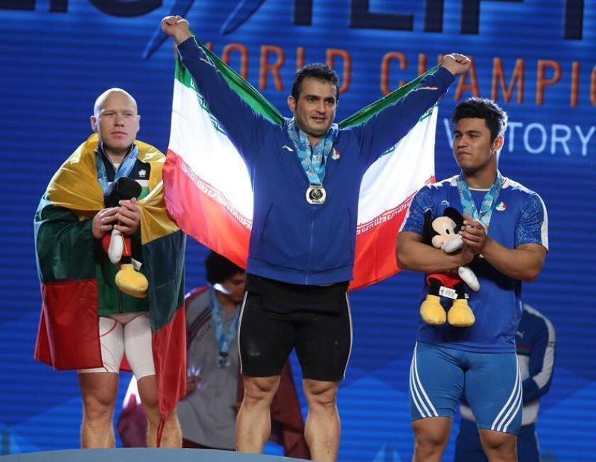 Sohrab Moradi from Iran (C) gold medalist, Aurimas Didzbalis from Lithuania (L), silver medalist and Seyedayoub Mousavijarahi from Iran (R), bronze medalist in the men's 95kg weight class in the total competition stand on the podium at the Weightlifting World Championships at the Anheim Convention Center in Anaheim, California. EFE