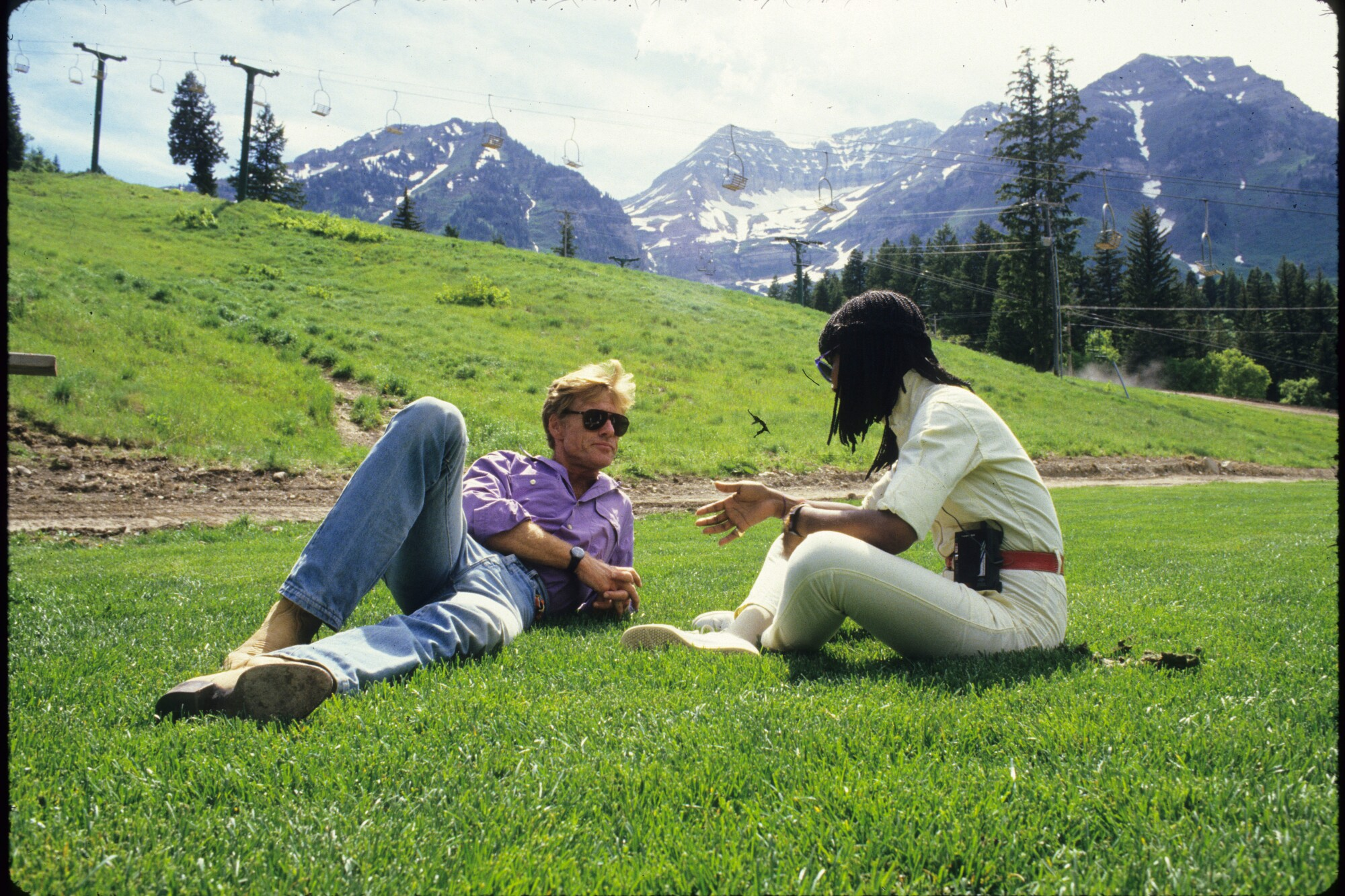 A man, left, and a woman chat in the grass with mountains in the background