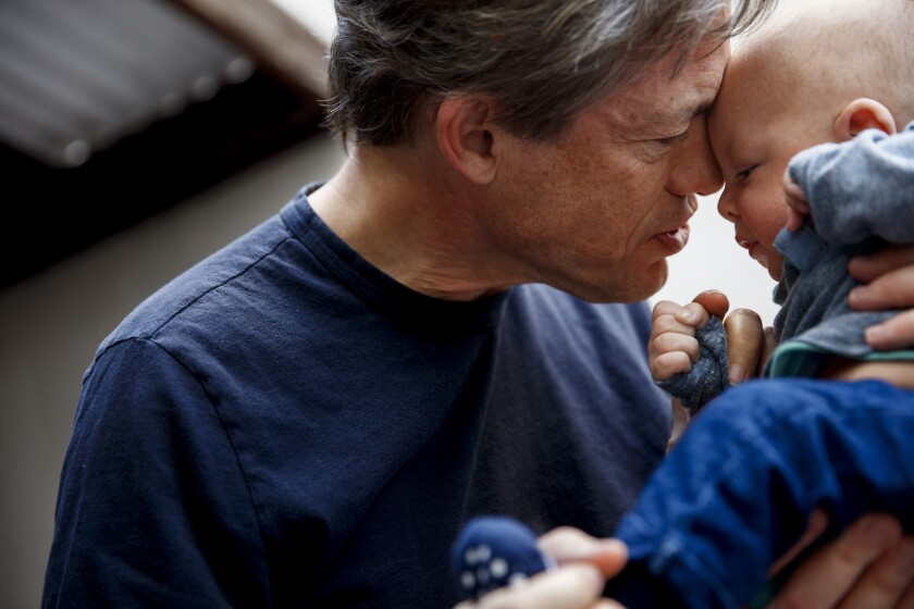 Berggruen cuddles his son Alexander following a passport photo session in w