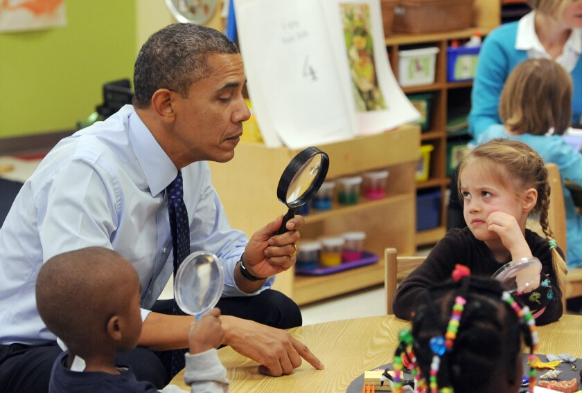 President Obama looks through a spy glass as a little girl stares at him during a visit to College Heights Early Childhood Learning Center in Decatur, Ga.