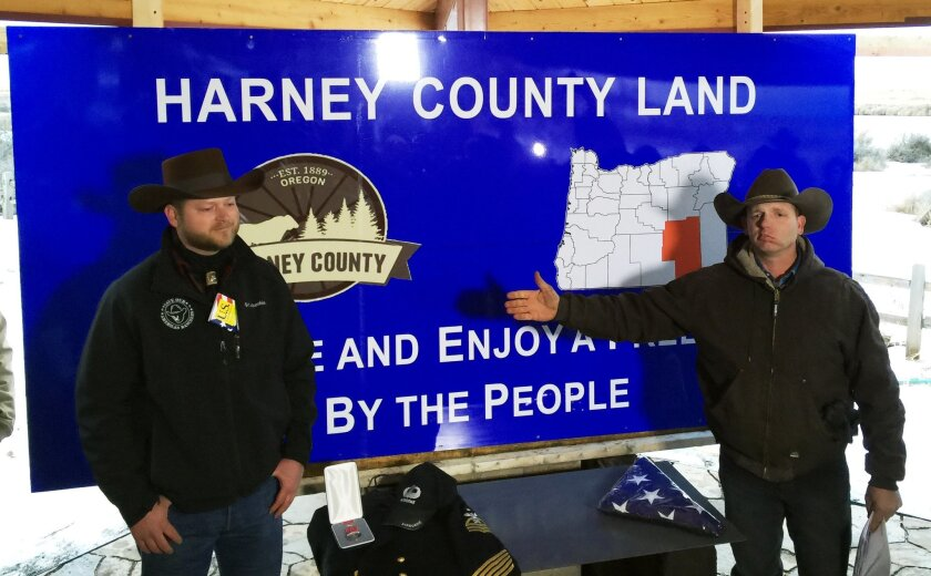 ADDS IDENTIFICATION OF ADRIAN SEWELL- Ryan Bundy, right, gestures toward Adrian Sewell at the Malheur National Wildlife Refuge in near Burns, Ore., Saturday, Jan. 23, 2016. Bundy, part of an armed group occupying the refuge to protest federal land policies, says the sign will be displayed on a road leading to the area. (AP Photo/Keith Ridler)