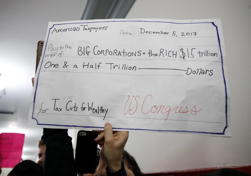 A man holds up a sign protesting the GOP tax plan on Capitol Hill.