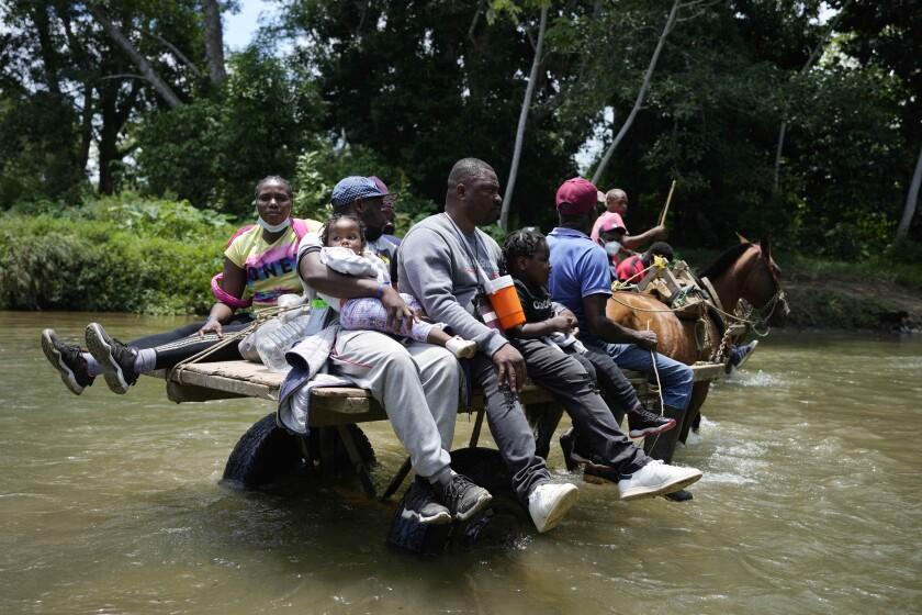 Migrantes cruzan el Río Acandi cerca de Acandi en Colombia el 14 de septiembre del 2021. Los migrantes, en su mayoría haitianos, tratan de llegar a Darién en Panamá y de allí partir hacia Estados Unidos. (Foto AP/Fernando Vergara)