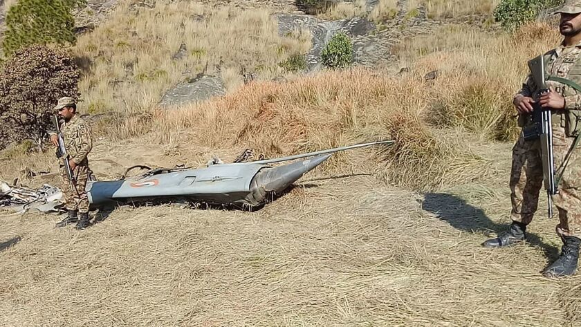 Pakistani soldiers stand next to what Pakistan says is the wreckage of an Indian fighter jet shot down Wednesday in Kashmir.